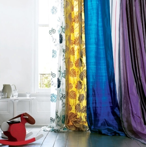 I love the thought of using many bright colored curtains all on one rod and letting them pool down onto the floor